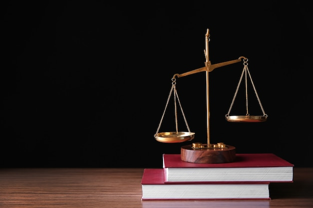 Justice scales and books on wooden table and black surface
