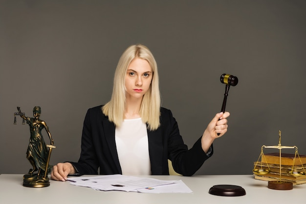 Justice scales, justice hammer and litigation document, female lawyer working at lawyer office.