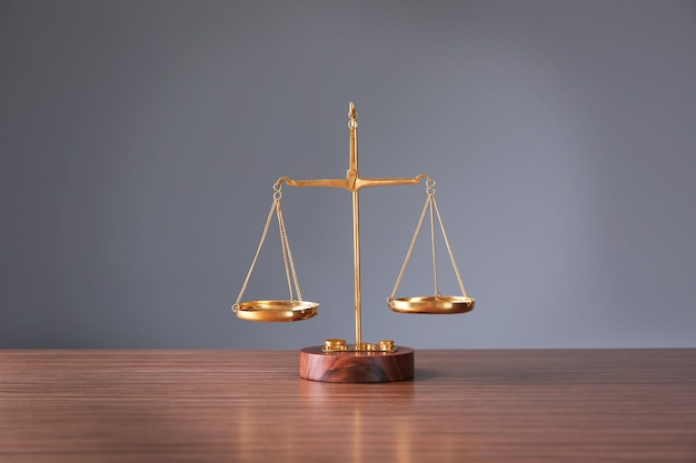 Justice scales on wooden table and  grey