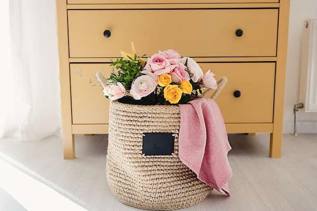 A jute handmade basket with a chalk board to write on with flowers and a pink towel inside it on the floor next to a yellow wooden dresser with drawers on a white wall cozy home