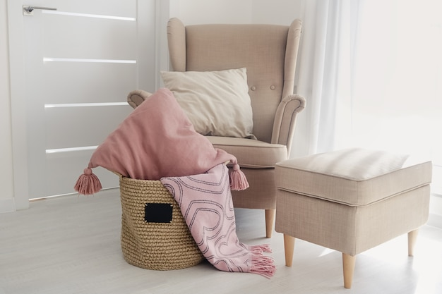 A jute handmade basket with a small black chalkboard and pillows and a pink blanket on the floor next to a beige armchair  with a pouf on a white wallpaper surface. cozy home concept