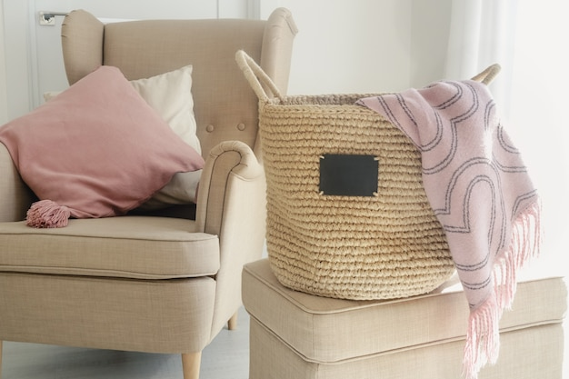 A jute handmade basket with a small black chalkboard and pink blanket on a pouf next to a beige armchair with pillows on a white wallpaper surface. cozy home concept