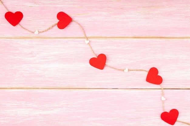 Jute rope with red glitter hearts and confetti hearts on pink background