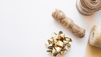 Jute string; golden bow and rolled up weaving ribbon on white background