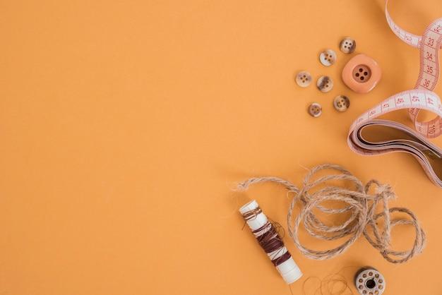 ジュートスレッド。ボタン;測定テープとスプールの色付きの背景
