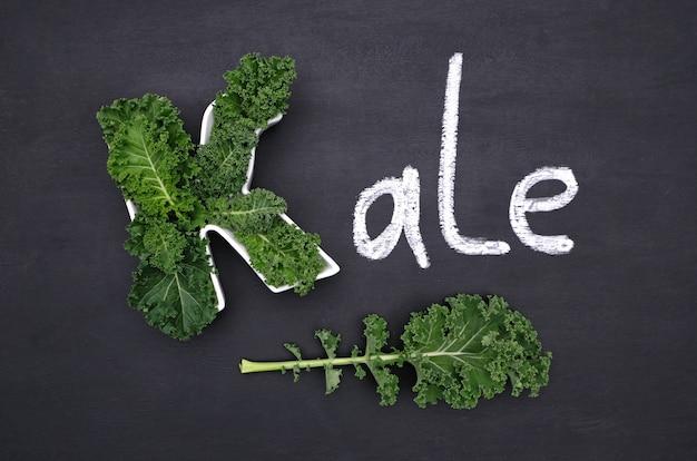 Листья капусты кудрявые внутри в форме буквы k, мелом надпись kale на доске. здоровая пища