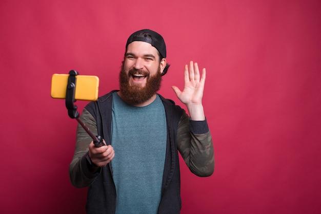Фотография счастливого человека, делающего селфи на фоне пина k