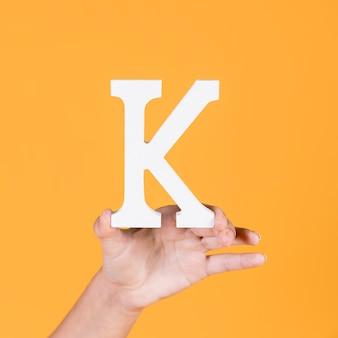 大文字のアルファベットkを持っている女性の手