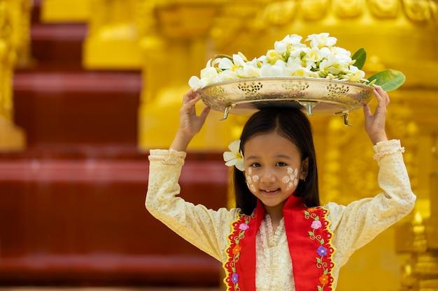 月の民族衣装を着た少女は、宗教的な日に僧kに捧げるために花の大きさのトレイを提示しています。