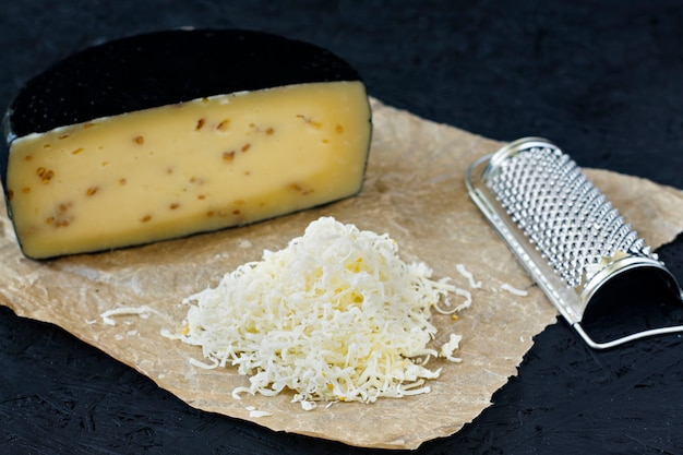 Kachotta cheese sliced on a black background with a grater