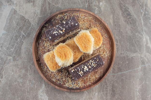 Barretta di waffle al cioccolato kadayif su un piatto di legno su marmo.
