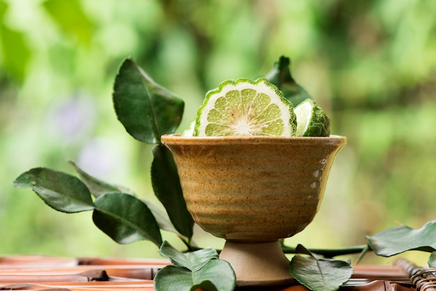 Kaffir lime or leech lime fruits and green leaves on an old wood .