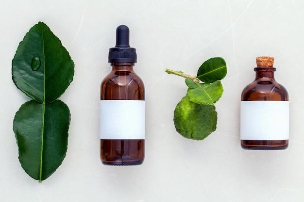 代わりのヘルスケア新鮮なkaffir llime葉と大理石の背景に油。