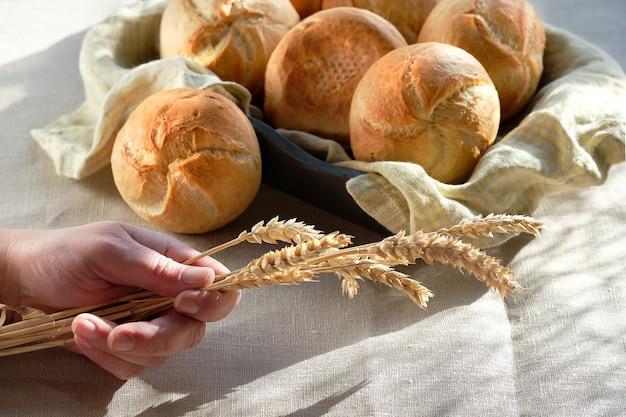 Кайзерские или венские булочки в корзине для хлеба с льняным полотенцем. стол накрыт скатертью песочного цвета.