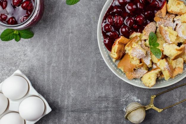 Кайзершмаррен или кайзершмаррн - это традиционный австрийский или немецкий сладкий блинный десерт с сахарной пудрой и ягодами, вишневым соусом или вареньем из грутце.