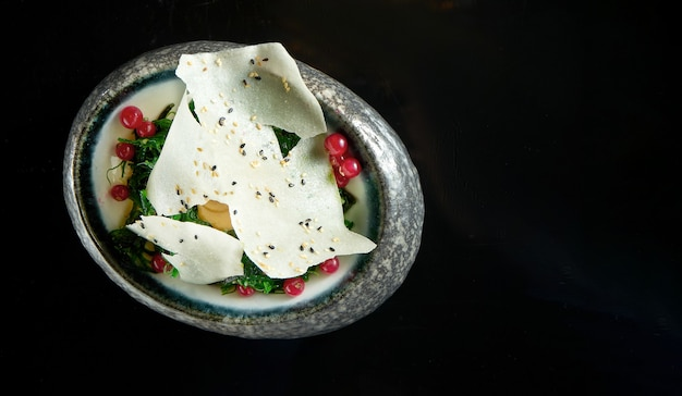 Салат кайсо с арахисовым соусом и рисовыми чипсами, подается в белой миске. салат из морских водорослей - вакамэ. изолированные на черном столе. ресторанная еда. японская кухня