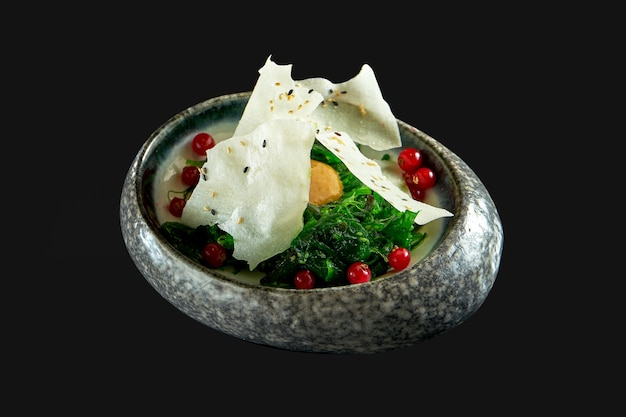 Kaiso salad with peanut sauce and rice chips served in a white bowl seaweed salad  wakame