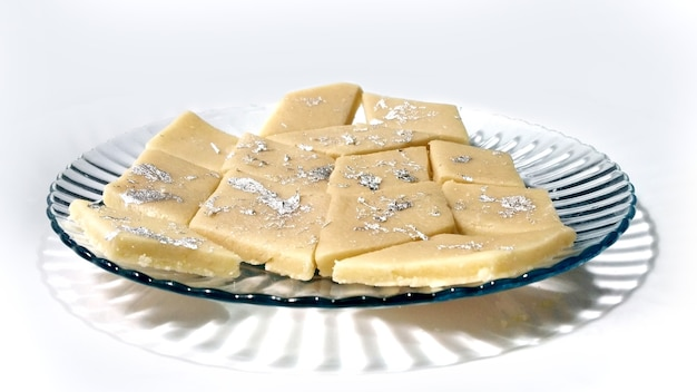 Kaju katli는 흰색 배경에 분리된 접시에 캐슈 설탕과 마바를 사용하여 만든 다이아몬드 모양의 인도 과자입니다. 선택적 초점