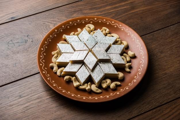 Каджу катли - индийская сладость в форме ромба, приготовленная из сахара кешью и мава, которая подается в тарелке на мрачной поверхности. выборочный фокус