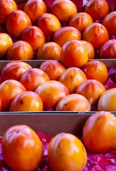 Куча свежих фруктов kaki на стойле рынка. фруктово-овощной рынок