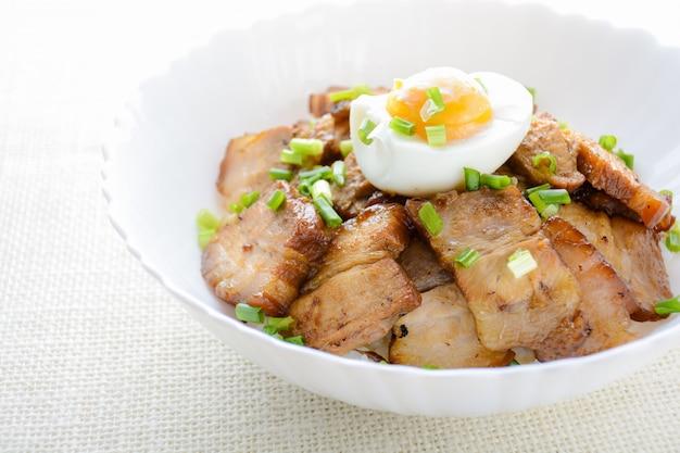 Чаша из риса с тушеной свиной грудинкой и вареным яйцом, японское название kakuni-don
