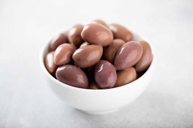 Kalamata olives in white bowl on white surface