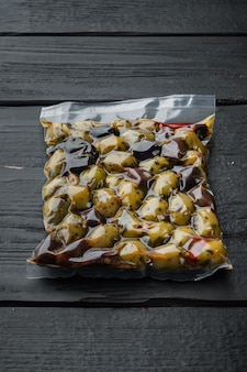 Kalamata olives with herbs, on black wooden table