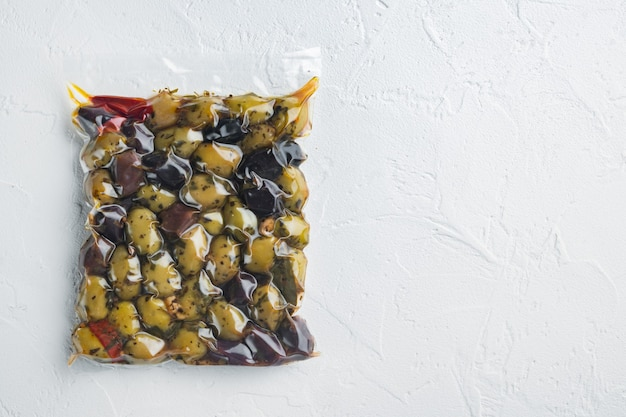 Kalamata olives with herbs, on white background, flat lay  with copy space for text