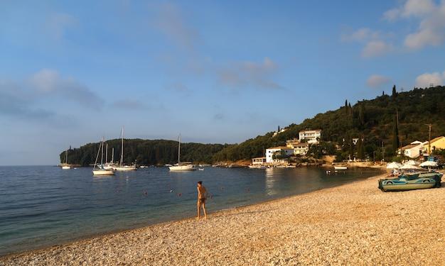 코르푸 섬 그리스 모래 해변에 칼라미 베이 바다에 들어가는 젊은 여자 소녀