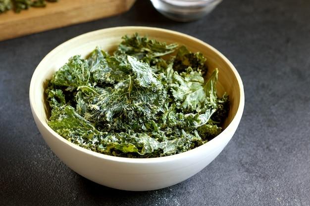 Kale chips in bowl on black background