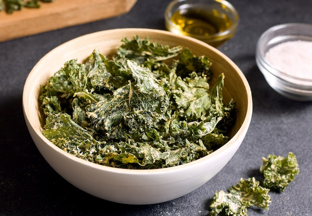 Kale chips in a bowl on a black table