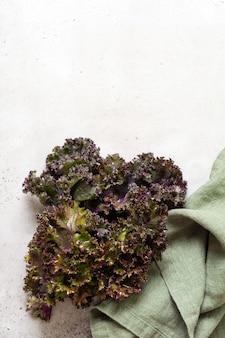 케일은 밝은 회색 슬레이트, 돌 또는 콘크리트 배경의 커팅 보드에 신선한 녹색 곱슬을 남깁니다. 선택적 초점입니다. 건강한 채식 음식.