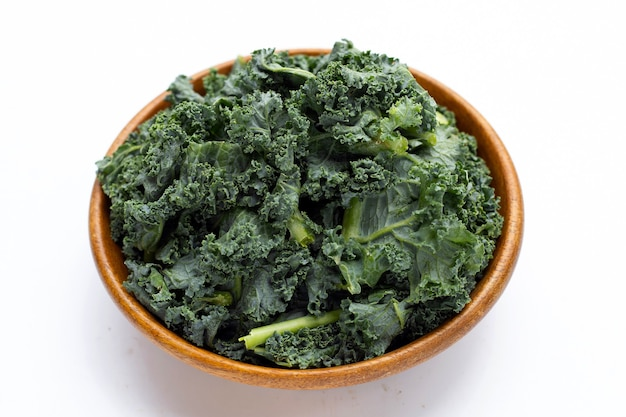 Kale leaves in wooden bowl on white background.