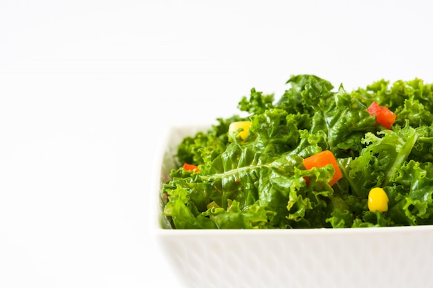 Kale salad in bowl with carrot, pepper and sweet corn isolated on white copy space