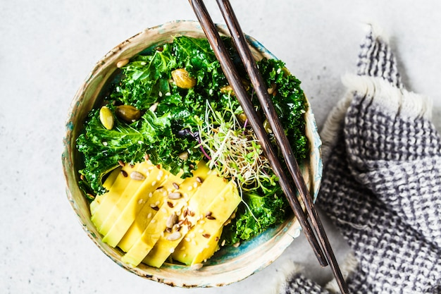 Kale salad with avocado and sprouts in a bowl, healthy vegan food concept,