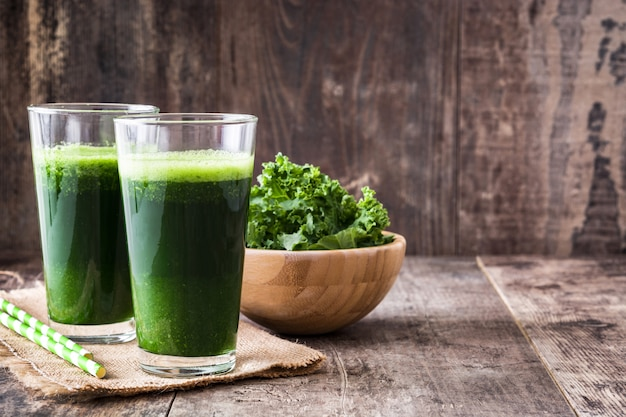 Kale smoothie in glass on wooden copy space