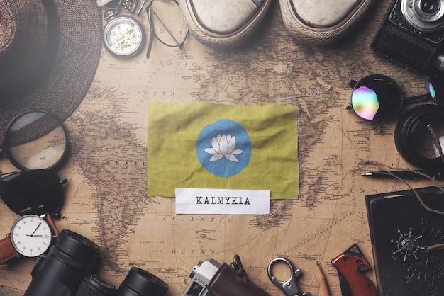 Kalmykia flag between traveler's accessories on old vintage map. overhead shot