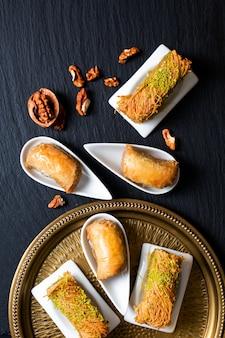 Концепция питания восточные арабские десерты, пахлава, грецкие орехи и рулет kanafeh на черной грифельной доске