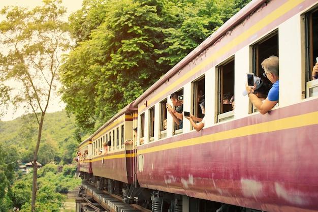 カンチャナブリ-タイ、2018年8月20日:カンチャナブリのクワイ川を渡る死の鉄道橋を走る列車をツアーするときに選択的な焦点の観光客が写真を撮る