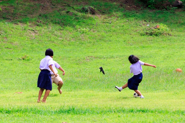 Kanchanaburi, thailand -august 25, 2017: thai student playing football on green field in the school.