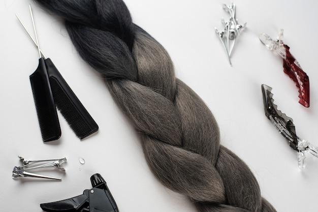 Канекалон черные волосы на белой поверхности с гребнями и аксессуарами для волос
