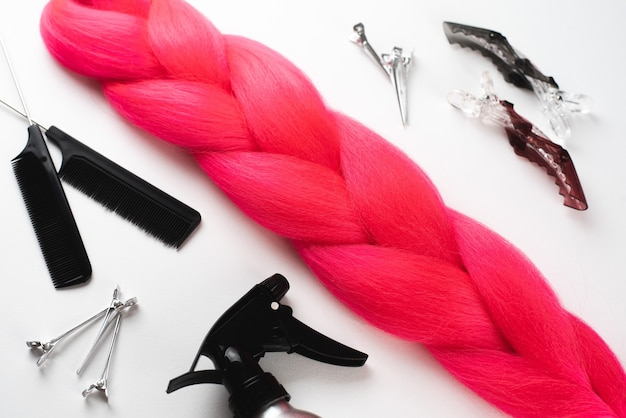 櫛とヘアアクセサリーを備えた白い表面のカネカロン深紅色の髪