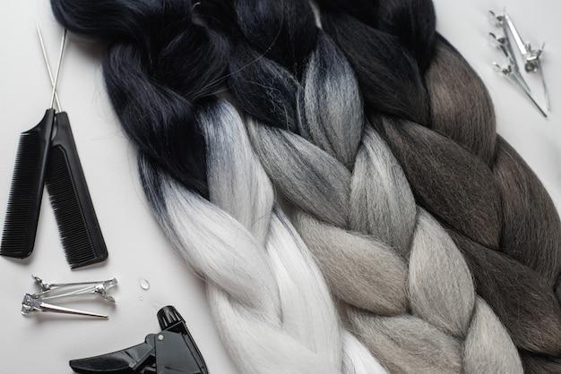 Канекалон для волос на белой поверхности с гребнями и аксессуарами для волос