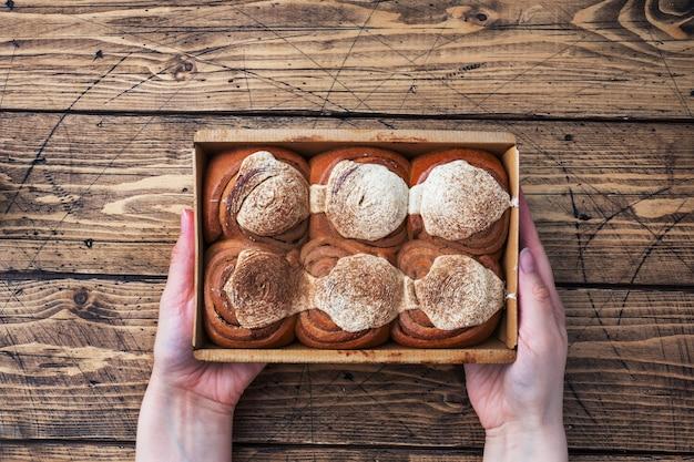 素朴な木製のテーブルにバタークリームを添えたカネルブルシナモンロール。自家製の焼きたてのペストリー。上面図、コピースペース。