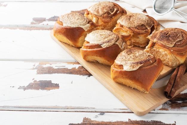 素朴な木製のテーブルにバタークリームを添えたカネルブルシナモンロール。自家製の焼きたてのペストリー。