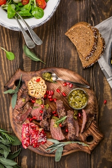 Kangaroo meat steak with green pesto and pomegranate on wooden cutting board.