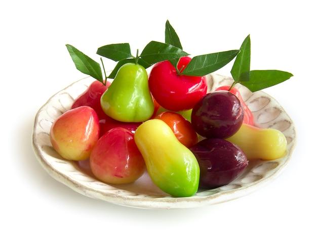 Тайский десерт удаляемый имитация фруктов - карамель kanom look, сделанная из размешанной фасоли, смешанной с сахаром и кокосовым орехом, покрытой стеклянным желе, вид сбоку на белом фоне