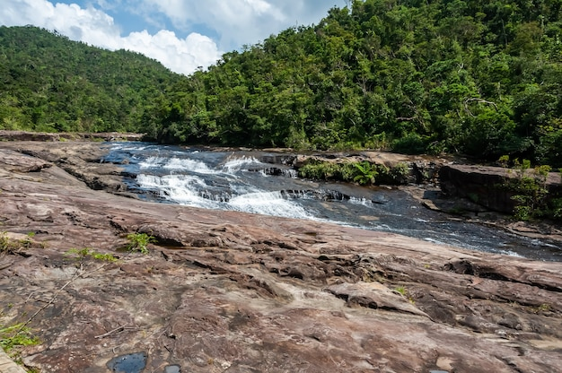 Kanpire waterfall flowing over a stone platform on the jungle