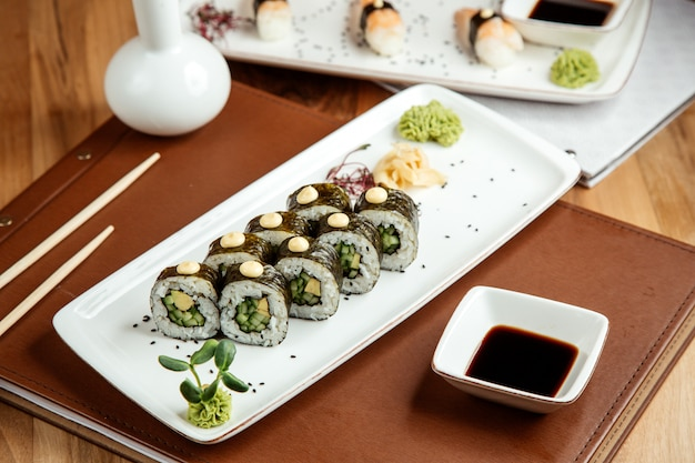 Kappa maki with nori avocafo ginger wasabi and soy sauce on table