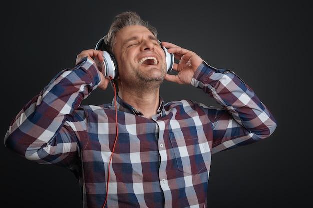 1 인용 노래방. 일부 음악을 듣고 회색 배경에 고립 서있는 동안 그의 새 장치의 크고 강력한 소리를 즐기는 매력적인 잘 생긴 남자 영감